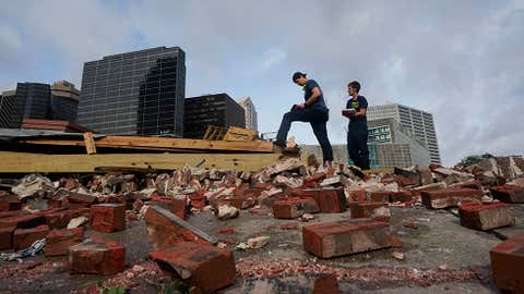 New Orleans firefighters assess damage on Monday, August 30, 2021, as they look through debris where a building collapsed from the effects of Hurricane Ida in New Orleans. (AP Photo/Eric Gay)