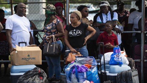 Evacuees wait to board a bus heading to an evacuation shelter in Nassau, Bahamas on Monday, September 9, 2019, after getting off a ferry from Marsh Harbour on Abaco island in the aftermath of Hurricane Dorian. (Andrew Caballero-Reynolds/AFP/Getty Images)