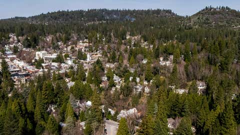 Downtown Nevada City is surrounded by a dense forested area, which increases its fire risk. City officials agree that the wooded draws, steep hillsides, narrow residential streets, ancient homes and thick urban tree canopy that define the character of the city also make it particularly at risk if a fire burns through. (Hector Amezcua/The Sacramento Bee via AP)