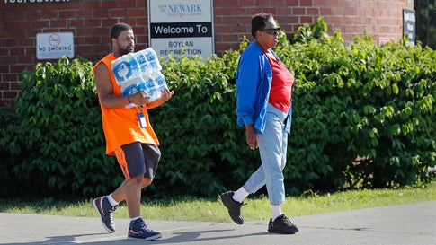 People leave the Boylan Street Recreation Center with cases of bottled water, Monday, August 12, 2019, in Newark, New Jersey, after recent U.S. Environmental Protection Agency tests showed elevated levels of lead in the drinking water in some areas of Newark, despite filters that had been distributed earlier. (AP Photo/Kathy Willens)
