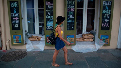 A woman walks past a cigar lounge and bar with sandbags lining in the French Quarter in preparation for tropical storm Barry in New Orleans, Louisiana, on July 11, 2019. - Tropical storm Barry barreled toward rain-soaked New Orleans on July 11 as the city hunkered down for an ordeal that evoked fearful memories of 2005's deadly Hurricane Katrina. Barry is predicted to become a Category 1 hurricane before making landfall Saturday with maximum winds reaching 75 mph. (Photo by Seth HERALD / AFP)        (Photo credit should read SETH HERALD/AFP/Getty Images)
