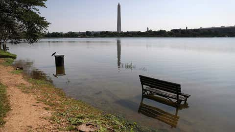 Nuisance flooding during a high tide spreads water around a park bench and sidewalk along the Tidal Basin in Washington on July 2, 2019.  That year, Washington had about 42 fewer nuisance flooding days because of decreased tidal range, a University of Central Florida study found. (Photo by Mark Wilson/Getty Images)