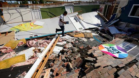 Benjamin Luna helps recover items from the children's wing of the First Pentecostal Church that was destroyed by Hurricane Laura, Thursday, August 27, 2020, in Orange, Texas. (AP Photo/Eric Gay)