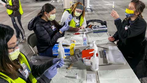Medical professionals from Oregon Health & Science University load syringes with the Moderna COVID-19 vaccine at a drive-thru vaccination clinic in Portland, Oregon on Sunday, January 10, 2021. The U.S. is entering the second month of the largest vaccination effort in history with a massive expansion of the campaign, opening up football stadiums, major league ballparks, fairgrounds and convention centers to inoculate a larger and more diverse pool of people. (Kristyna Wentz-Graff/Pool Photo via AP)