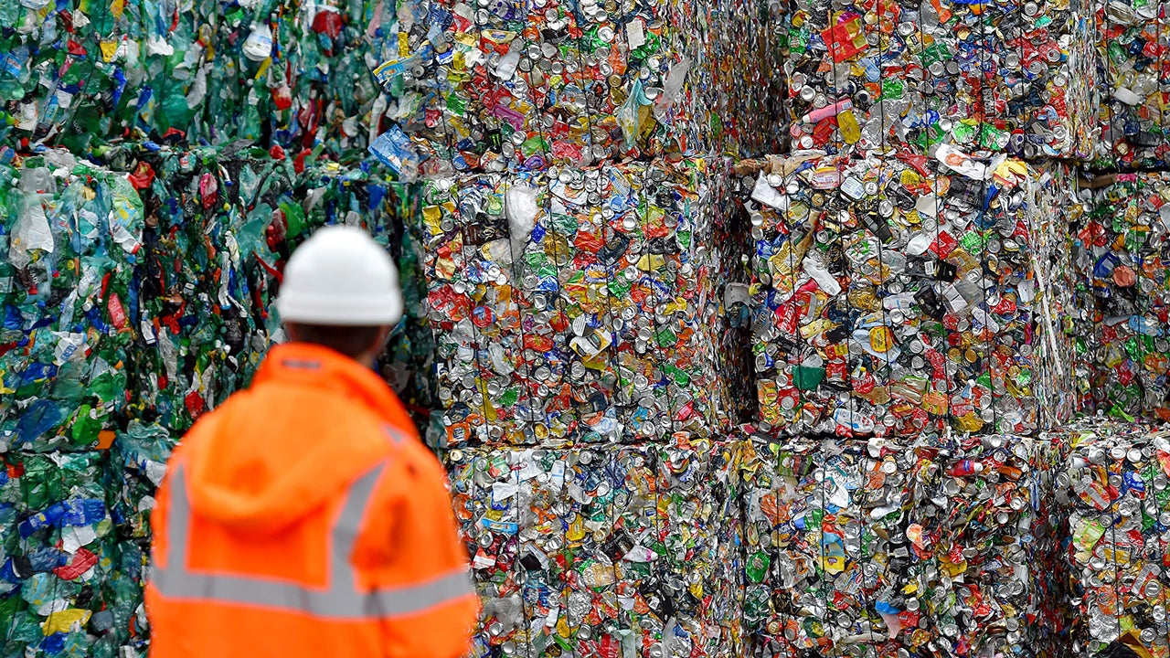 An employee walks through plastic waste waiting to be recycled on August 21, 2018, at a sorting center in Ploufragan, western France. (Loic Venance/AFP/Getty Images)
