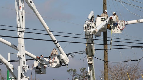 Utility workers repair the electrical grid after Hurricane Michael on October 16, 2018, in Panama City, Florida. (Photo by Joe Raedle/Getty Images)