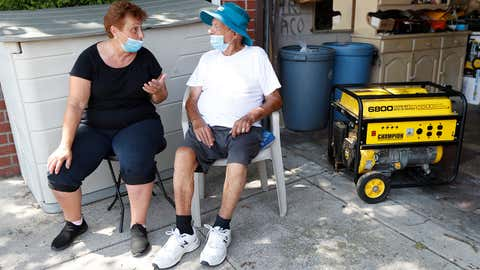 Caretaker Elena Bogdanov, left, sits with Carmelo Caruana, 86, as they wait for Caruana's grandson to bring gas for one of their generators, on Wednesday, August 5, 2020, in the Middle Village neighborhood of Queens, in New York, after losing power Tuesday when Tropical Storm Isaias blew through the area. (AP Photo/Kathy Willens)