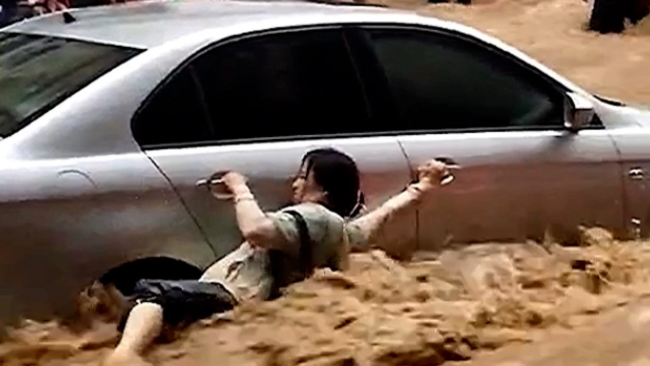 Woman Clings to Car in China's Devastating Flooding