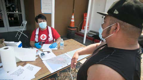 August 22, 2020. Santa Rosa, California.Red Cross shelter at the Sonoma County Fairgrounds in Santa Rosa, California. Omar Padilla is asked Covid-19 health screening questions by Red Cross volunteer Cristian Calvillo before entering the shelter.Photo by Dennis Drenner/American Red Cross