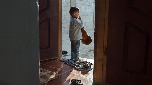 A Syrian refugee stands in the doorway of his family's home in eastern Jordan, which his father and uncles built using YouTube tutorials. The child comes from a family of Syrian farmers from Hama. (Sharon Avraham)