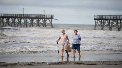Mary McCants, left, and Amy Garrett walk along the beach in Cherry Grove, South Carolina, on Tuesday, August 4, 2020, near the Sea Captain Pier that was damaged by Hurricane Isaias. (Photo by Sean Rayford/Getty Images)