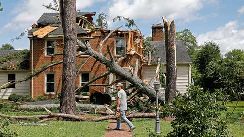 A man walks past a damaged house with a chainsaw in the Riverview neighborhood of Suffolk, Virginia, after Hurricane Isaias moved through the region Tuesday, August 4, 2020. (Jonathon Gruenke/The Daily Press via AP)