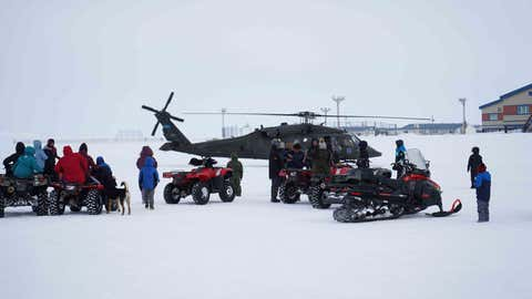 Community members of the City of Chevak watch from a safe distance as representatives from of the Alaska Department of Military and Veterans Affairs, the Department of Environmental Conservation, and the Department of Commerce, Community, and Economic Development load onto an Alaska Army National Guard UH-60 Black Hawk helicopter in Chevak, Alaska, April 9, 2021. Members of the Alaska Department of Military and Veterans Affairs, the Department of Environmental Conservation, and the Department of Commerce, Community, and Economic Development traveled to Western Alaska April 7-9 to meet with Tribal leaders and citizens in Bethel, Tuluksak, and Chevak to discuss disaster assistance measures and processes in light of recent emergencies that have occurred in the region, and in preparation for the upcoming flood season. (U.S. Army National Guard photo by Dana Rosso)