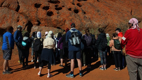 Visitors begin the Mala Walk trail at Uluru on August 12, 2019, in the Uluru-Kata Tjuta National Park, Australia. According to Parks Australia Uluru has welcomed 244,075 visitors this calendar year, an increase of 18.7%. (Lisa Maree Williams/Getty Images)