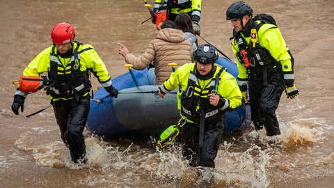 Firefighters with the Winston-Salem Fire Department evacuate residents at Creekwood Apartments as flood waters rise on Thursday, November 12, 2020, in Winston-Salem, North Carolina. (Andrew Dye/The Winston-Salem Journal via AP)