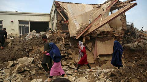 Afghan family walk near to the damaged houses after after a mudslide during heavy flooding in the Parwan province, north of Kabul, Afghanistan, Wednesday, Aug. 26, 2020. The flooding in northern Afghanistan killed and injured dozens of people officials said Wednesday. (AP Photo/Rahmat Gul)