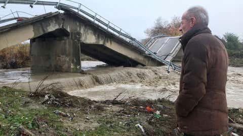 Local resident Nue Shkreta looks at a collapsed bridge at the entrance of his village, Mamuras, northern Albania, Friday, Dec. 1, 2017. (AP Photo/Florent Bajrami)