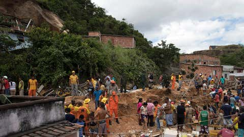 """Residents, volunteers and firefighters search the debris after a mudslide in Boa Esperanca or """"Good Hope"""" shantytown in Niteroi, Brazil, on Saturday, Nov. 10, 2018. (AP Photo/Leo Correa)"""