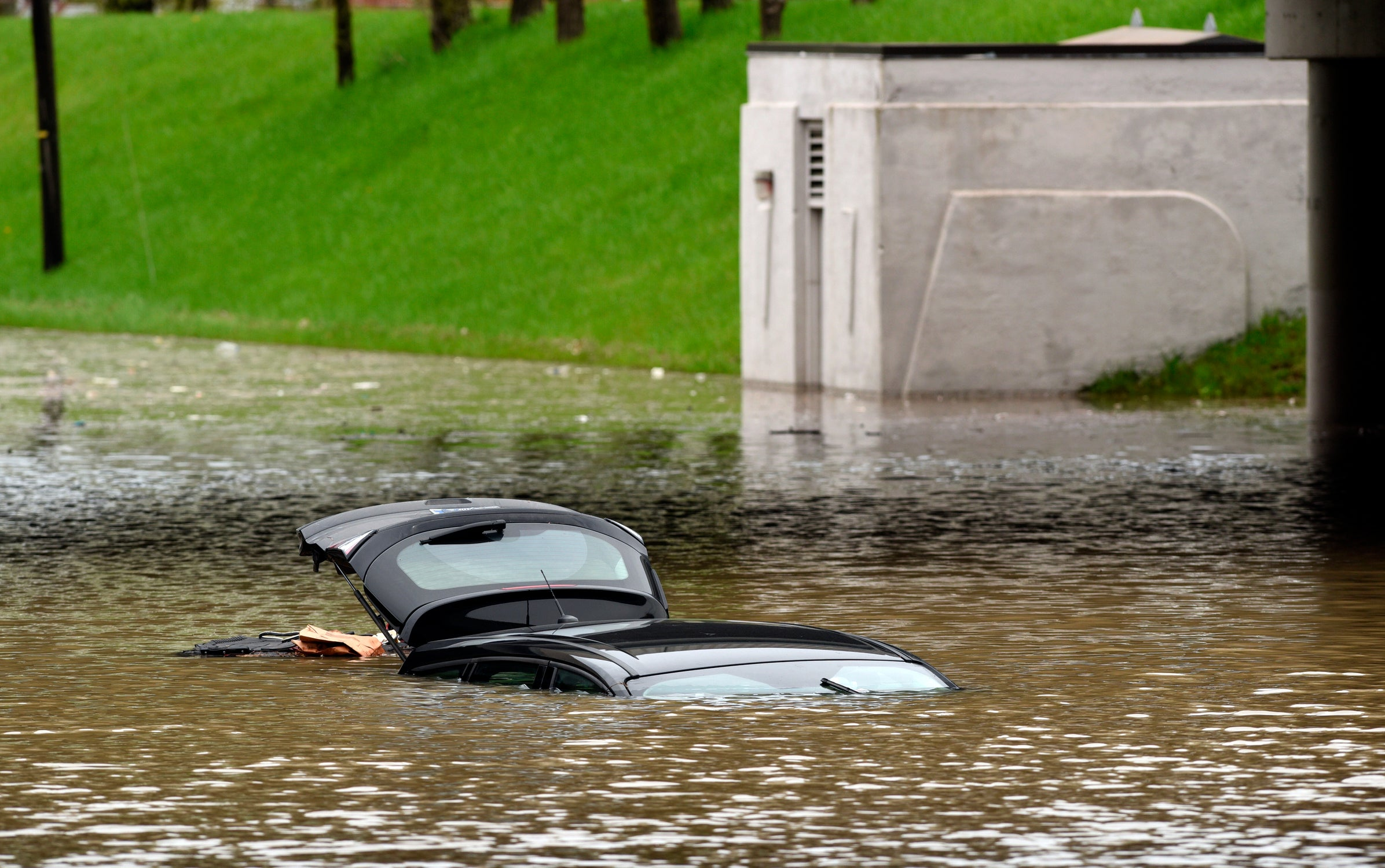 The roof and open hatch are the only visible signs of a vehicle submerged in floodwaters at the Monroe Blvd underpass at the Interstate 94 in Taylor, Mich., Wednesday, May 1, 2019. Overnight rain across the Detroit area lefts scores of basements flooded and made some local streets impassable. Some vehicles had to be towed from the water. (Max Ortiz/Detroit News via AP)