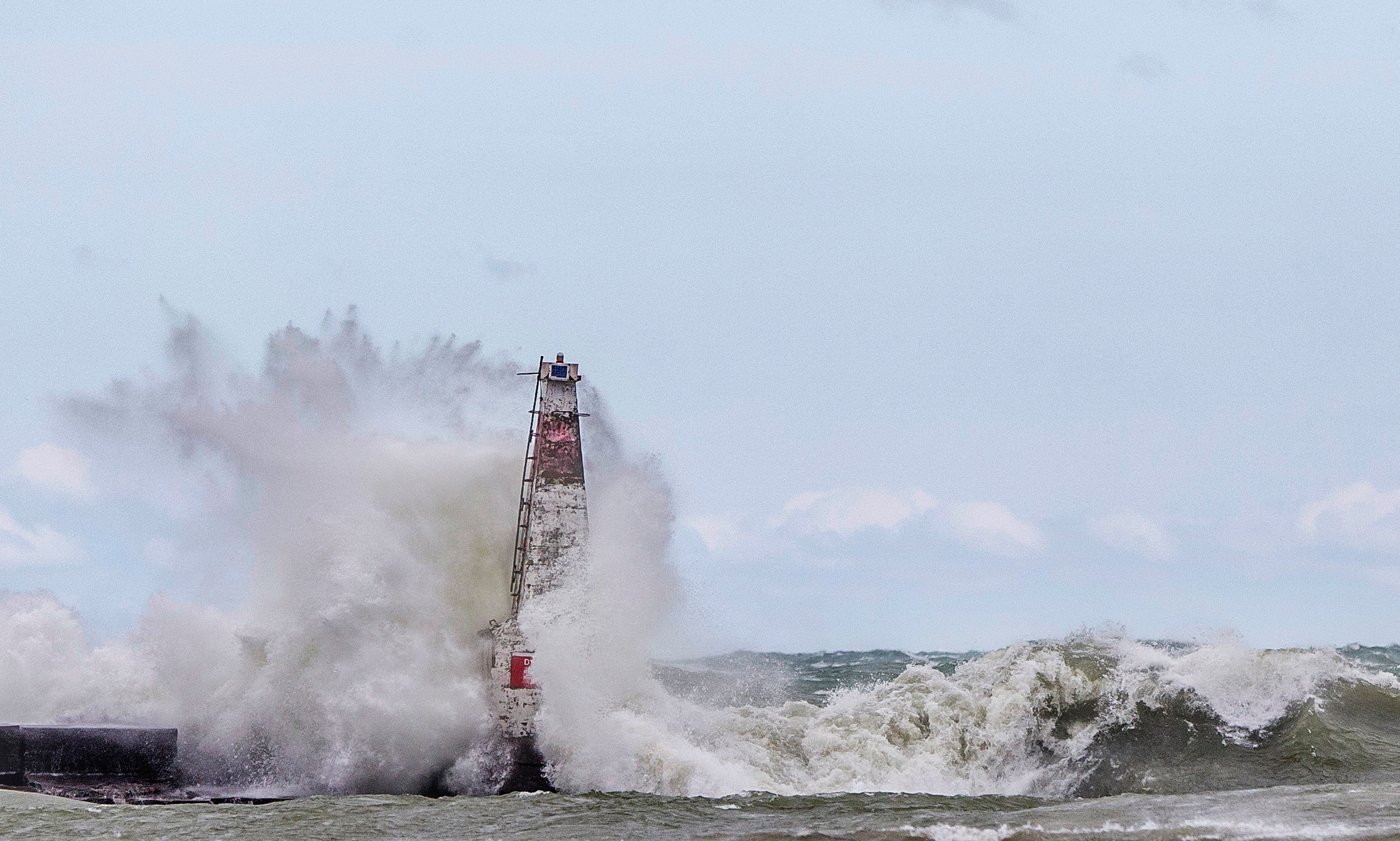 FILE - In this April 6, 2017 file photo, big waves crash against a breakwater light as strong winds create dangerous conditions on Lake Michigan, at Washington Park in Michigan City, Ind. Federal officials predict surging water levels across the Great Lakes and record highs in Lakes Superior and Erie over the next six months. A report Monday, May 6, 2019 from the U.S. Army Corps of Engineers says the lakes have been rising steadily for several years and are getting an extra boost as winter's melting snow mingles with recent heavy rainfall. It's a remarkable turnaround from early this decade, when lake levels were slumping and some hit record lows. (Robert Franklin/South Bend Tribune via AP, File)