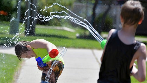 Jaxon Claymore, 8, left, and his older brother Jalen, 9, battle each other with large water guns in the hot mid-day sun in front of their apartment building on Wednesday, July 17, 2019, Bismarck, N.D. The pair say they compete against one another at home and in school to see who is the best in sports from running, throwing and strength. The weather forecast for the area calls for temperatures in the 80s with little chance of rain for the next several days. (Mike McCleary/The Bismarck Tribune via AP)