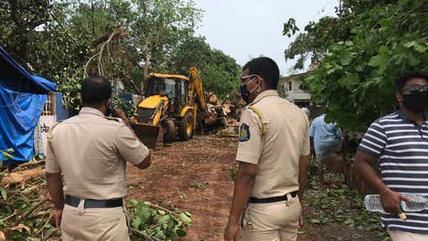 Authorities clear a tree that got uprooted in the rain and strong winds at Anjuna in western Goa state, India, Monday, May 17, 2021. Cyclone Tauktae, roaring in the Arabian Sea was moving toward India's western coast on Monday as authorities tried to evacuate hundreds of thousands of people and suspended COVID-19 vaccinations in one state. (AP Photo/Vineeta Deepak)