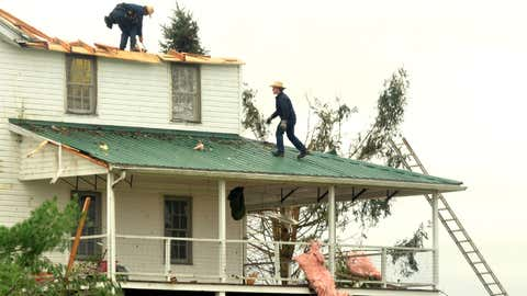 People work on clearing debris from a house damaged along Route 322 on Monday, Nov. 6, 2017, after severe weather damaged at least 20 homes in the Williamsfield Township, Ohio, area on Sunday evening. (Warren Dillaway/Star Beacon via AP)