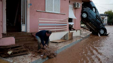 A man clears mud from his home in front of flipped over cars in the municipality of Mandra western Athens, on Wednesday, Nov. 15, 2017. (AP Photo/Petros Giannakouris)