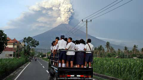 Students stand on a truck as they head to school with Mount Agung volcano spewing smoke and ash in Karangasem, Bali, Indonesia, Tuesday, Nov. 28, 2017. Mount Agung volcano on Bali has erupted for the first time in more than half a century, forcing closure of the Indonesian tourist island's busy airport as the mountain gushes huge columns of ash that are a threat to airplanes. (AP Photo/Firdia Lisnawati)