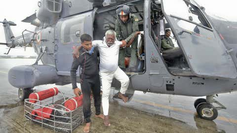 An Indian fisherman who was stranded in the Arabian Sea is escorted down from an Indian Navy helicopter after being rescued in Thiruvananthapuram, Kerala state, India, Friday, Dec. 1, 2017. (AP Photo)
