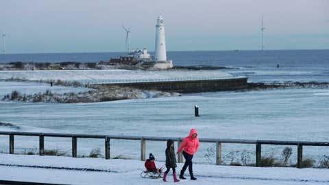People walk through snow on the coast at Whitley Bay, northeastern England, on Monday, Dec. 11, 2017. (Owen Humphreys/PA via AP)