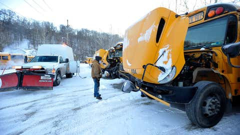 McIlwain School Bus Lines mechanic Terry Logue works on getting school buses started early, as he gets them ready to run before the drivers arrive on a frigid morning, Wednesday, Jan. 3, 2018, in Johnstown, Pa. (Todd Berkey/The Tribune-Democrat via AP)