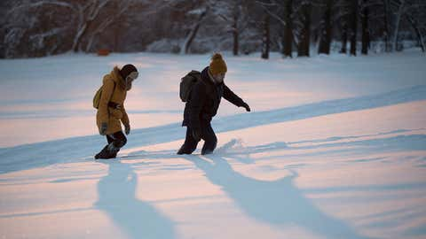 People struggle to move through the snow at sunset in Kolomenskoye park in Moscow, Russia, Tuesday, Feb. 6, 2018. More than a month's average of snow fell on Moscow over the weekend, with the height of snow now reaching up to 22 inches in some parts of the capital with the temperatures dropping down to 5 degrees Fahrenheit during the day and 1.4 degrees Fahrenheit at night. (AP Photo/Pavel Golovkin)