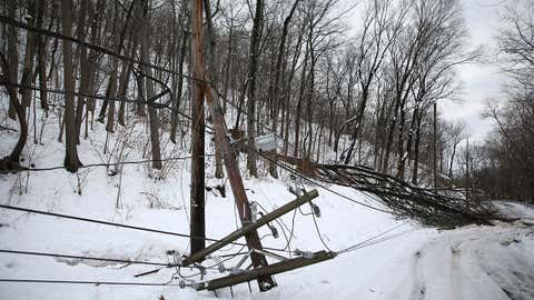 Fallen trees and a broken power pole block a road in Oakland, N.J., Thursday, March 8, 2018. (AP Photo/Seth Wenig)