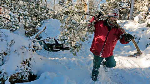 Peter Pelletier removes branches from the tree that fell onto his car parked at his home in Fairhaven, Mass., Wednesday, March 14, 2018. A third major snowstorm in two weeks buried some New England towns beneath 2 feet of snow. (Peter Pereira/Standard Times via AP)