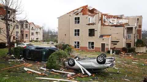 Two cars are turned over in front of a storm damaged apartment complex, Tuesday, March 20, 2018, after a violent storm went through Jacksonville, Ala., Monday night. (AP Photo/Brynn Anderson)