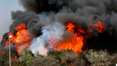 In this Tuesday, April 17, 2018, heavy smoke billows from burning trees after a wildfire broke out in a farm field along US Highway 183 about 10 miles south of Seiling, Okla. (Jim Beckel/The Oklahoman via AP)