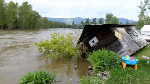 A shed on the banks of the Kettle River falls into the river in Grand Forks, British Columbia, on Thursday, May 17, 2018. (Jonathan Hayward/The Canadian Press via AP)