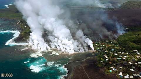 This image taken from video on Monday, June 4, 2018, and provided by the U.S. Geological Survey shows lava from a fissure flowing into the ocean at Kapoho Bay at Kapoho on the island of Hawaii. After overrunning the town overnight and destroying hundreds of homes, the lava flowed into the shallow bay and had nearly filled it. (U.S. Geological Survey via AP)