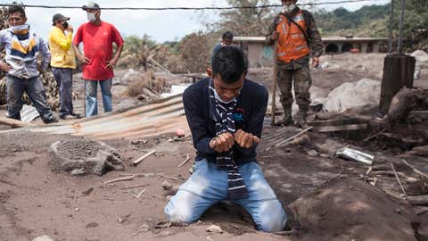 """Bryan Rivera cries after looking at the remains of his house, after his family went missing during the Volcan de Fuego or """"Volcano of Fire"""" eruption, in San Miguel Los Lotes, Guatemala, Thursday, June 7, 2018. Guatemala's national disaster agency suspended search and rescue efforts at the zone devastated by the eruption, saying climatic conditions and still-hot volcanic material makes it dangerous for the rescuers. (AP Photo/Moisés Castillo)"""