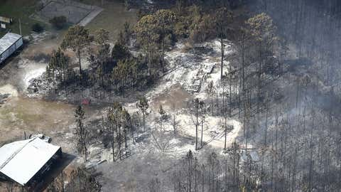This aerial photo shows smoke where a wildfire, still smoldering, ripped through the area consuming more than 20 homes in Eastpoint, Fla. Monday, June 25, 2018. (Joe Rondone/Tallahassee Democrat via AP)