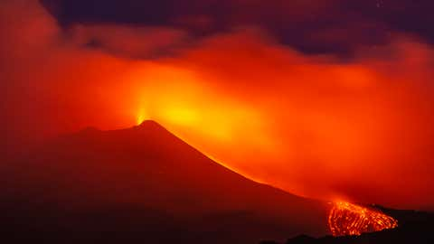 """Mount Etna volcano spews lava during an eruption early Saturday, August 25, 2018. Mount Etna in Sicily has roared back into spectacular volcanic action, sending up plumes of ash and spewing lava. Italy's National Institute of Geophysics and Volcanology (INGV) says that the volcano, which initially """"re-awoke"""" in late July, sprang into fuller action Thursday evening by shooting up chunks of flaming lava as high as 150 meters (500 feet) almost constantly. (AP Photo/Salvatore Allegra)"""