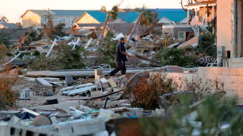 Henry Penafiel, a member of the FEMA emergency response, walks amid ruin in the aftermath of Hurricane Michael in Mexico Beach, Fla., Saturday, Oct. 13, 2018. (AP Photo/Gerald Herbert)
