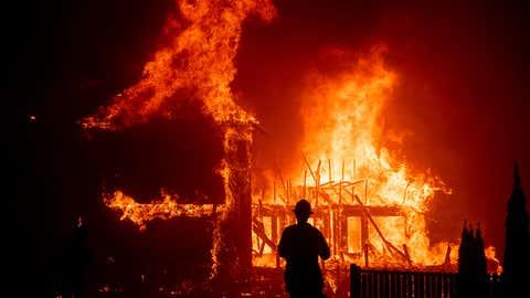 A home burns as the Camp Fire rages through Paradise, California, on Thursday, Nov. 8, 2018. (AP Photo/Noah Berger)