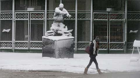 Commuters walks by the statue of famed Chicago Cubs broadcaster Harry Carey in front of Wrigley Field Monday, Nov. 26, 2018, in Chicago. A wintry storm brought blizzard-like conditions to parts of the Midwest early Monday, grounding hundreds of flights and causing some road traffic chaos as commuters returned to work after the Thanksgiving weekend. (AP Photo/Kiichiro Sato)