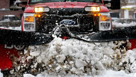 A snow plow driver clears snow in a parking lot on Monday, Nov. 26, 2018, in Okemos, Michigan. (Nick King/Lansing State Journal via AP)