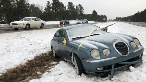 Vehicles pass a stranded Jaguar in the median of U.S. 1 in Raleigh, N.C., on Monday, Dec. 10, 2018. Gentle snow turned to sleet, then rain Monday, and was expected to freeze overnight. (AP Photo/Allen G. Breed)