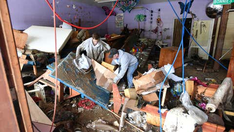 Mick McGuinn, right, and his son Michael McGuinn help clean up Mick's girlfriend's store Bonnie Sew Good as flood waters from the Russian River continue to recede in Guerneville, Calif., on Friday, March, 1, 2019. (AP Photo/Josh Edelson)