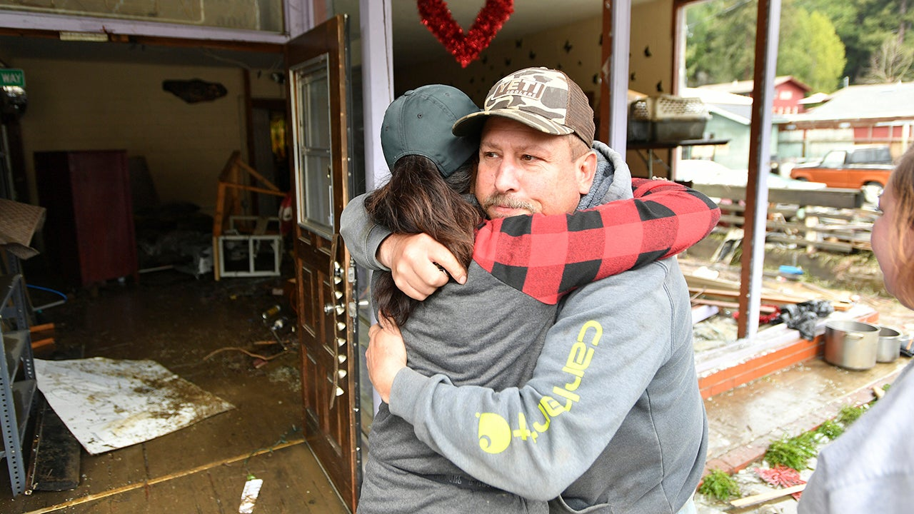Guerneville resident Pete Swinney, right, hugs shop owner Bonnie Plevney as they talk about her ruined shop Bonnie Sew Good in Guerneville, Calif., on Friday, March 1, 2019. Authorities have reopened the roads into two towns cut off for days by a rain-swollen river and residents and work crews have started cleaning up the muck that flooding left behind. (AP Photo/Josh Edelson)