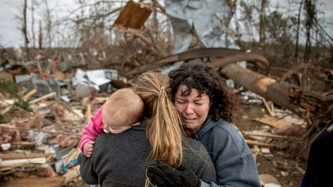 """Carol Dean, right, cries while embraced by Megan Anderson and her 18-month-old daughter Madilyn, as Dean sifts through the debris of the home she shared with her husband, David Wayne Dean, who died when a tornado destroyed the house in Beauregard, Ala., Monday, March 4, 2019. """"He was my wedding gift,"""" said Dean of her husband whom she married three years ago. """"He was one in a million. He'd send me flowers to work just to let me know he loved me. He'd send me some of the biggest strawberries in the world. I'm not going to be the same."""" (AP Photo/David Goldman)"""